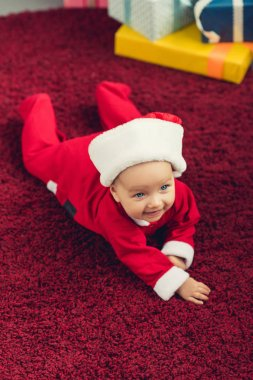 Adorable little baby in santa suit lying on red carpet stock vector