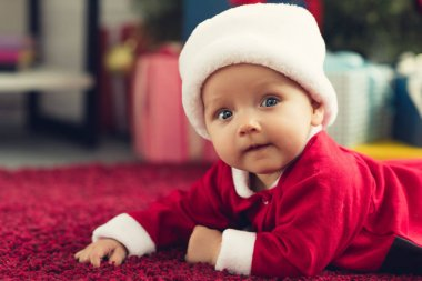 close-up portrait of adorable little baby in santa hat lying on floor and looking at camera