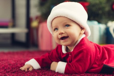 happy little baby in santa suit lying on red carpet with christmas gifts blurred on background