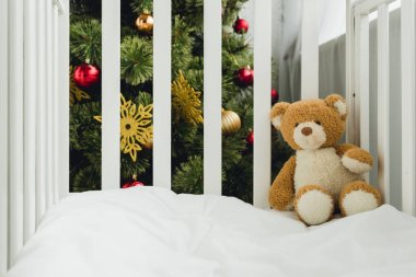 Teddy bear in infant bed in front of christmas tree stock vector