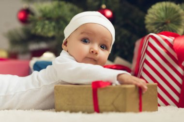 close-up portrait of adorable little baby lying on floor with christmas gifts and looking at camera