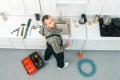 Fotografie high angle view of handsome plumber holding adjustable wrench and looking at camera in kitchen