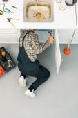 Fotografie Erhöhte Ansicht des Klempners reparieren defekte Waschbecken mit verstellbaren Schraubenschlüssel in Küche
