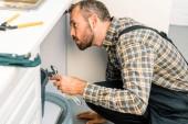 Seitenansicht des hübschen Klempners mit verstellbarem Schraubenschlüssel und Blick unter kaputte Spüle in der Küche