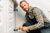 Photo handsome plumber holding adjustable wrench near kitchen cabinet and looking at camera