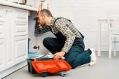 Fotografie gut aussehend Klempner holding verstellbaren Schraubenschlüssel und suchen unter defekten Spüle in der Küche