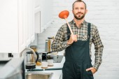 Photo cheerful handsome plumber holding plunger on shoulder and looking at camera in kitchen