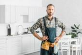 schöner Klempner in Overalls und Werkzeuggürtel, der in der Küche in die Kamera schaut
