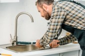 Photo handsome plumber repairing tap with monkey wrench in kitchen