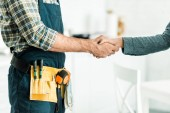 Fotografie ořízne obraz instalatér a klient třesoucíma se rukama v kuchyni
