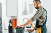 boční pohled pohledný instalatér užívat nástroje z panelu nástrojů v kuchyni