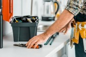 Photo cropped image of plumber putting tools on kitchen counter in kitchen