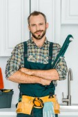 Photo handsome plumber holding monkey wrench and looking at camera in kitchen