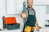 Fotografie smiling handsome plumber showing monkey wrench in kitchen