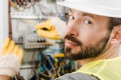 schöner bärtiger Elektriker repariert Stromkasten, benutzt Schraubenzieher im Flur und schaut in die Kamera