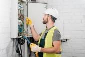 boční pohled elektrikáře drží schránky a kontrola vodičů v elektrické pole v chodbě