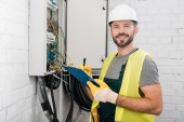 Photo smiling handsome electrician holding clipboard near electrical box in corridor and looking at camera