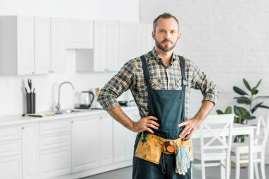 handsome plumber in overalls and tool belt looking at camera in kitchen