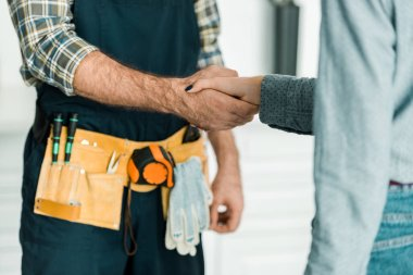 cropped image of plumber and customer shaking hands in kitchen