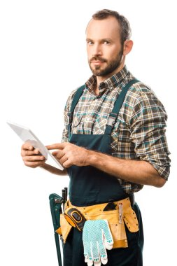 Handsome plumber with tool belt using digital tablet isolated on white and looking at camera stock vector