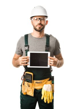 handsome electrician holding tablet with blank screen isolated on white and looking at camera