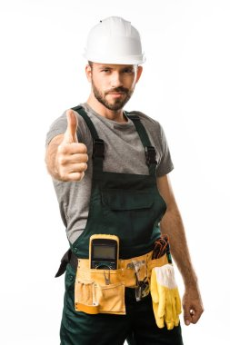 handsome electrician showing thumb up and looking at camera isolated on white