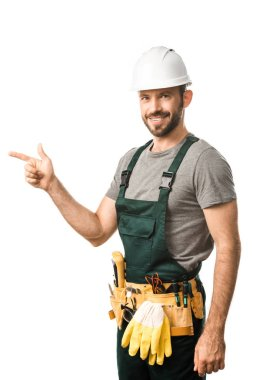 smiling handsome electrician pointing on something isolated on white