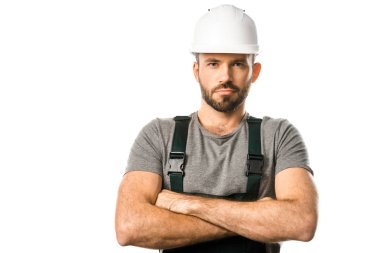 handsome plumber in helmet standing with crossed arms and looking at camera isolated on white