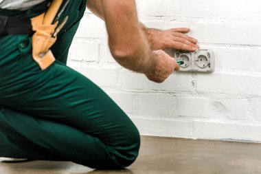 cropped image of electrician unscrewing power socket with screwdriver at home