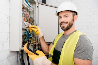 smiling handsome electrician checking electrical box with multimetr in corridor and looking at camera