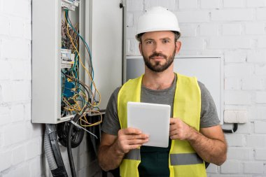 handsome electrician holding tablet near electrical box in corridor and looking at camera