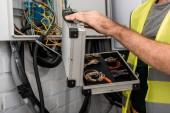 immagine ritagliata di toolbox detenzione elettricista vicino alla scatola elettrica nel corridoio