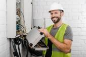 sorridere della casella degli strumenti della holding elettricista vicino alla scatola elettrica nel corridoio e rivolto verso lobiettivo
