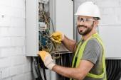 sorridente bello elettricista che ripara la scatola elettrica con le pinze in corridoio e rivolto verso lobiettivo