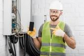 usmíval se pohledný elektrikář směřující na smartphone s prázdnou obrazovku poblíž elektrické pole v chodbě