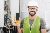 Lächelnder schöner Elektriker zeigt Smartphone mit leerem Bildschirm in der Nähe von Stromkasten im Flur