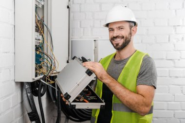 smiling electrician holding toolbox near electrical box in corridor and looking at camera