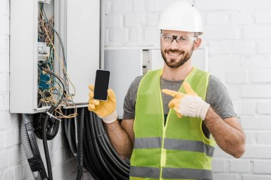 smiling handsome electrician pointing on smartphone with blank screen near electrical box in corridor