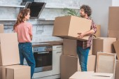 Photo couple unpacking cardboard boxes together at new kitchen
