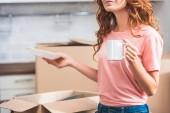 Fotografia immagine potata della donna con capelli rossi ricci che tiene tazza di caffè e piatto a casa nuova