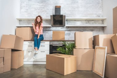smiling attractive woman sitting on kitchen counter between cardboard boxes and showing peace sign at new home