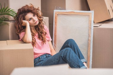 tired beautiful woman with curly red hair sitting on floor near cardboard boxes at new home