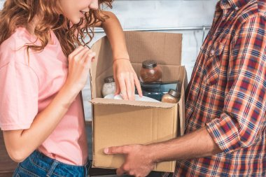 cropped image of couple unpacking utensil from cardboard box at new home