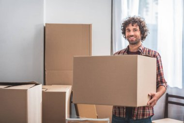 smiling handsome man with curly hair holding cardboard box at new home