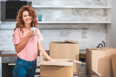 smiling beautiful woman holding cup of coffee and unpacking cardboard box at new home