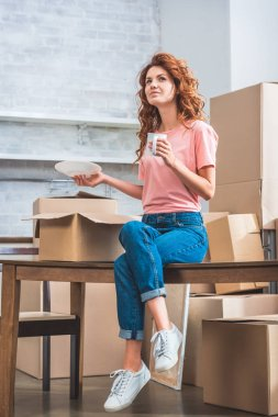 beautiful woman holding cup of coffee and plate, sitting on table with cardboard box at new home