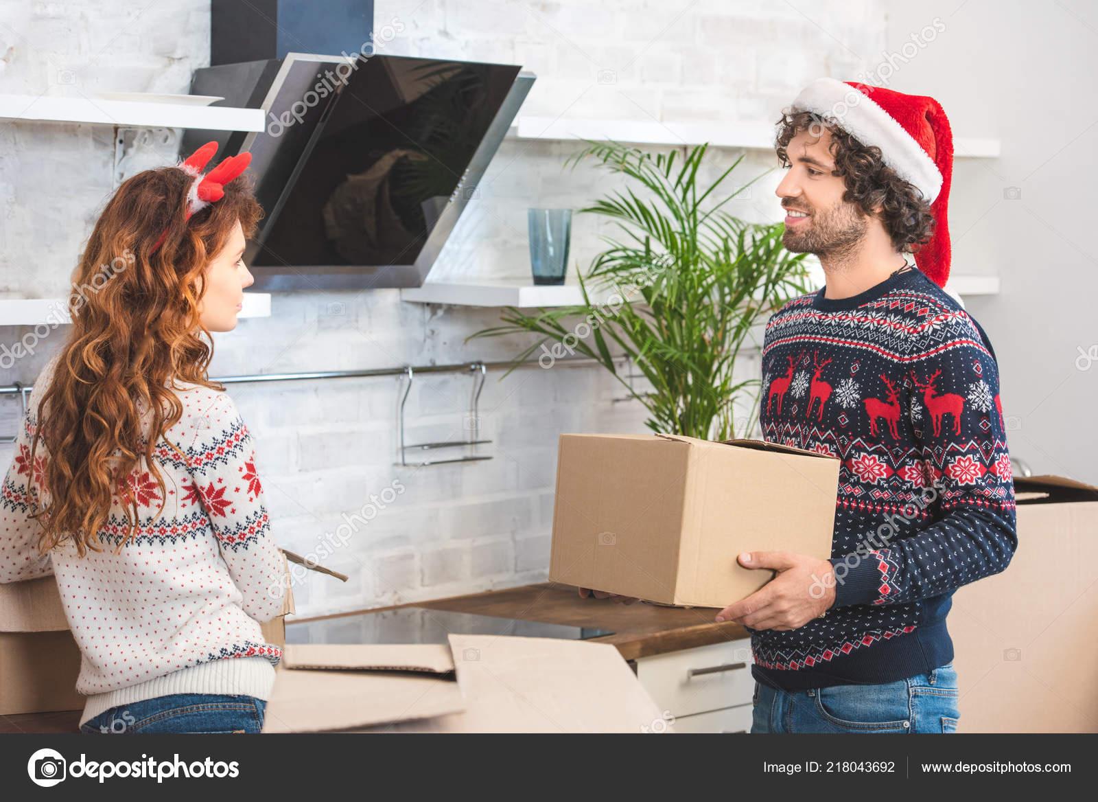 Gelukkige jonge paar uitpakken karton vakken nieuwe huis kerst