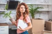 krásná žena s kudrnaté zrzavé vlasy drží v květináči a notebook v novém domově