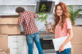 couple unpacking cardboard boxes at new home, girlfriend holding potted plant and looking at camera