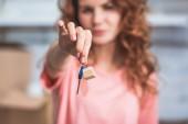 Fotografia vista ravvicinata della giovane donna che tiene la chiave dalla nuova casa
